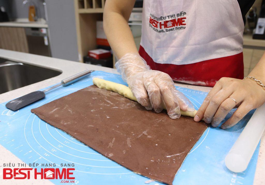 Cán phần bột nâu tương tự. Sau đó bạn đặt lần lượt một miếng bột nâu lên một miếng bột trắng hoặc ngược lại tùy thích, cuộn tròn hai phần bột này vào nhau cho đẹp mắt.